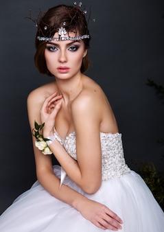 Mulher jovem noiva vestido de noiva no estúdio com maquiagem e penteado