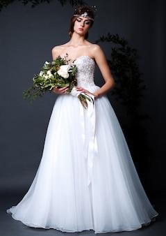 Mulher jovem noiva vestido de noiva no estúdio segurando flores com maquiagem e penteado