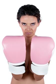 Mulher jovem nua com luvas de boxe rosa, retratando uma luta contra a conscientização do câncer de mama.
