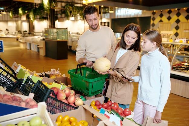 Mulher jovem, o marido e a filha escolhendo melão no supermercado