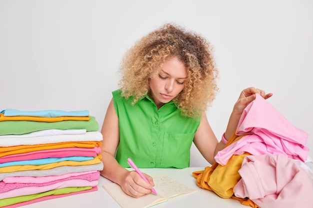 Mulher jovem ocupada com cabelo encaracolado escreve dicas sobre como cuidar das roupas no diário examina o material da roupa lavada antes de se lavar, senta na mesa pilha de roupas dobradas perto de vestimentas para evitar sangramento