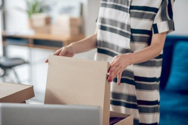 Mulher jovem ocupada preparando mercadorias para envio