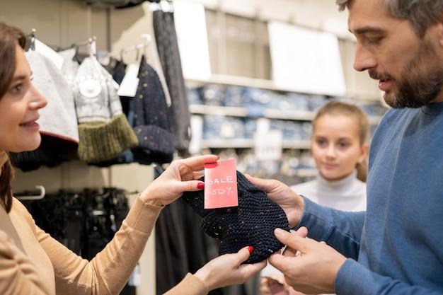 Mulher jovem oferecendo ao marido para experimentar um boné de malha preto que está à venda com 50% de desconto