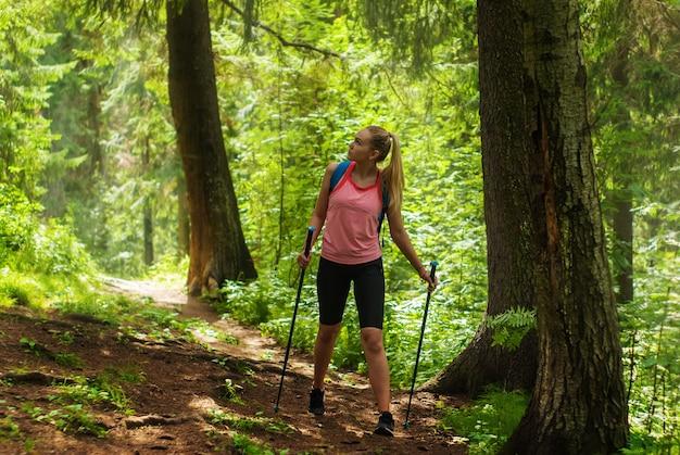 Mulher jovem olha ao redor enquanto caminha em uma trilha em uma floresta na montanha