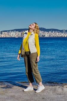 Mulher jovem olha para o céu enquanto caminha ao longo da costa do mar de mármara