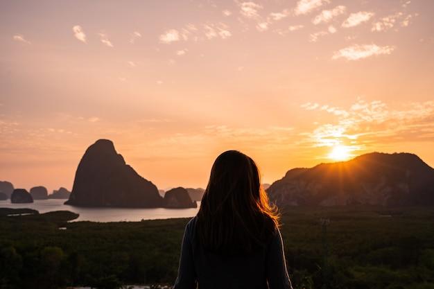 Mulher jovem olhando o nascer do sol sobre a montanha