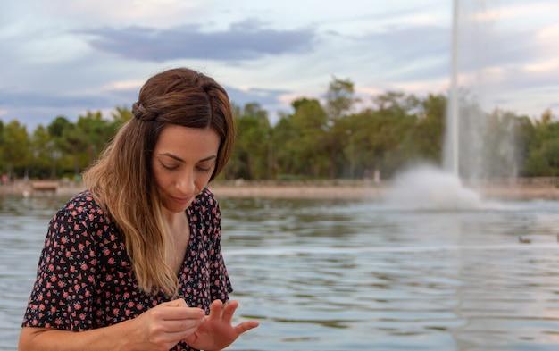 Mulher jovem olhando para as mãos em um lago com um fluxo de água. foco seletivo.