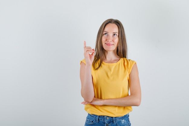 Mulher jovem olhando para cima com o dedo fazendo login na camiseta