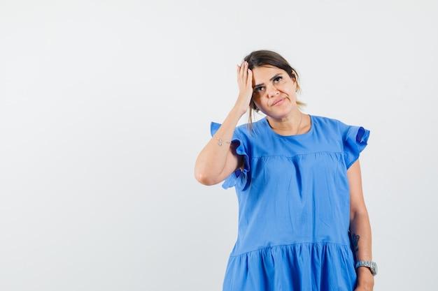 Mulher jovem olhando para cima com um vestido azul e parecendo pensativa