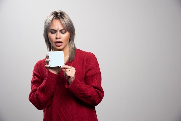 Mulher jovem olhando para o bloco de notas sobre fundo cinza.