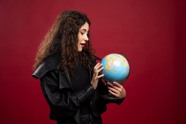 Mulher jovem olhando para o globo.