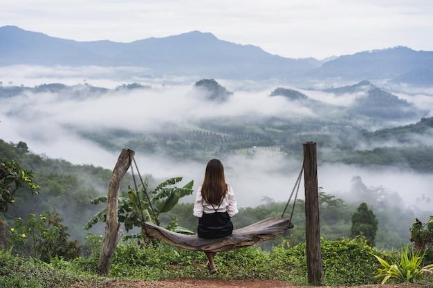 Mulher jovem olhando para o mar de névoa