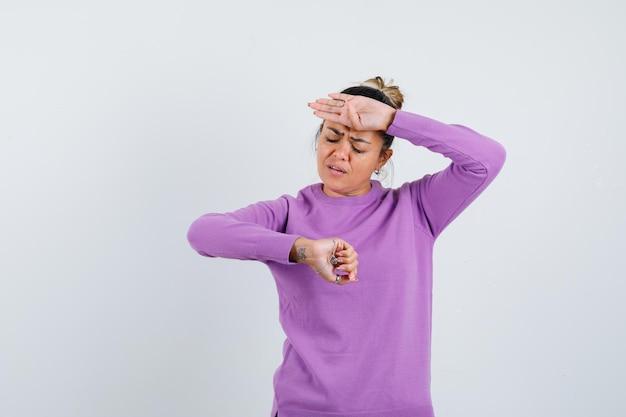 Mulher jovem olhando para o relógio enquanto coloca a mão na testa