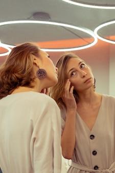 Mulher jovem olhando para seu reflexo no espelho grande.