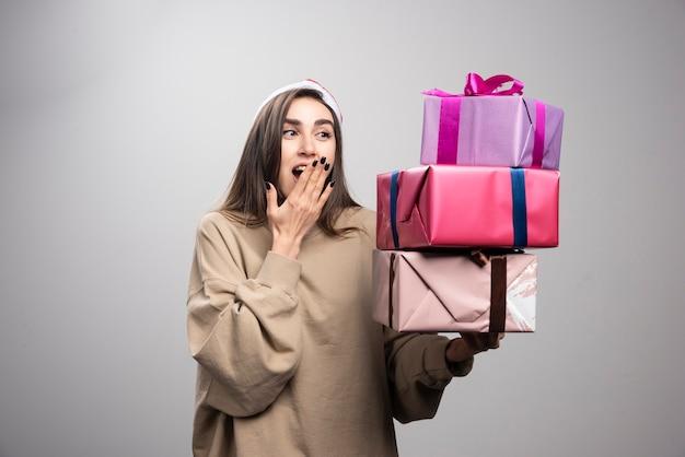 Mulher jovem olhando para três caixas de presentes de natal.