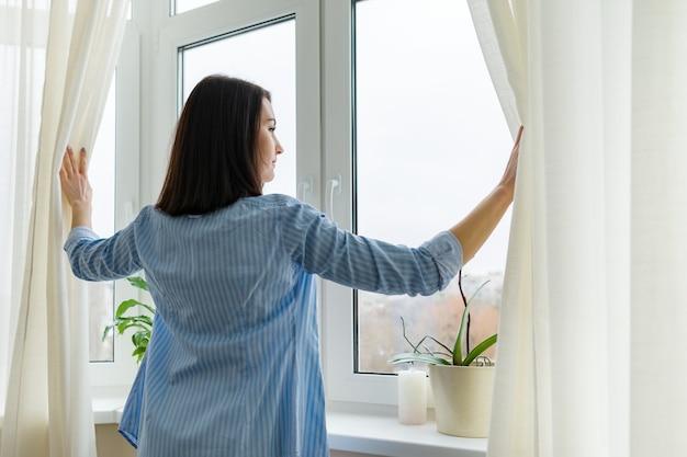 Mulher jovem olhando pela janela, dia nublado de inverno, mulher com camisa azul abrindo cortinas