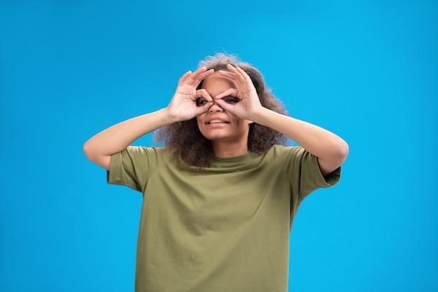 Mulher jovem olhando positivamente para a frente usando uma camiseta cor de pêssego mostrando os músculos isolados na parede azul