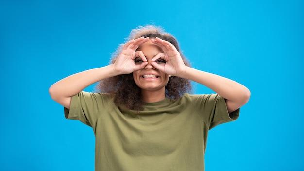 Mulher jovem olhando positivamente para a frente usando uma camiseta verde-oliva com binóculos isolados na parede azul