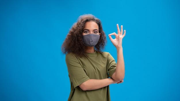 Mulher jovem olhando positivamente para a frente usando uma camiseta verde-oliva com os braços cruzados, isolados na parede azul