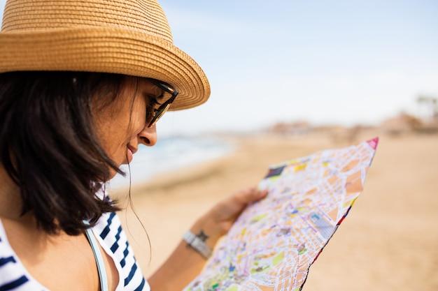 Mulher jovem, olhar, a, mapa, frente, a, mar