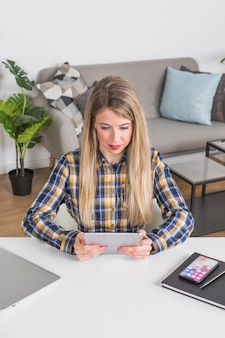 Mulher jovem, olhar, tablete digital, escrivaninha, em, interior lar