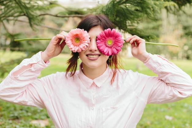 Mulher jovem, olhos cobertura, flores, e, sorrindo
