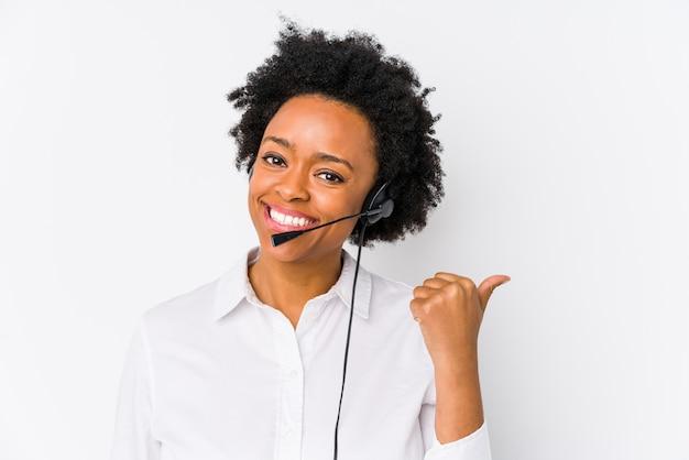 Mulher jovem operador de telemarketing americano africano pontos isolados com o dedo do polegar, rindo e despreocupado.