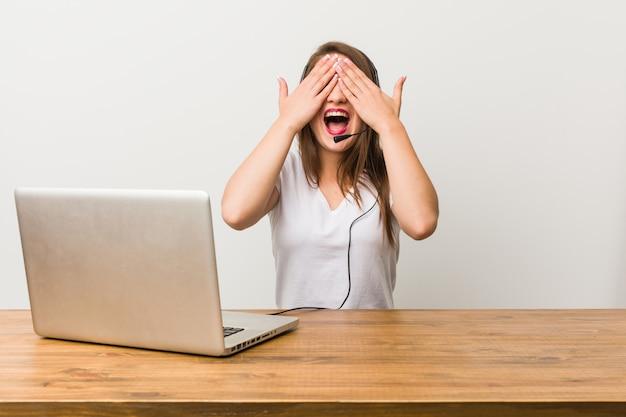 Mulher jovem operador de telemarketing cobre os olhos com as mãos, sorri amplamente esperando por uma surpresa.