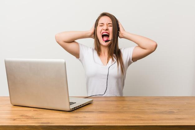Mulher jovem operador de telemarketing cobrindo os ouvidos com as mãos, tentando não ouvir som muito alto.
