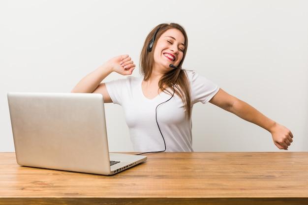 Mulher jovem operador de telemarketing dançando e se divertindo.