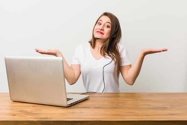 Mulher jovem operador de telemarketing duvidando e encolher os ombros os ombros em questionar o gesto.