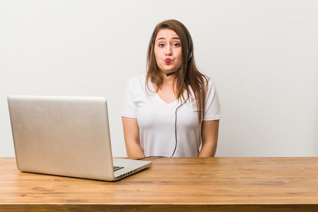 Mulher jovem operador de telemarketing encolhe os ombros e abre os olhos confusos.