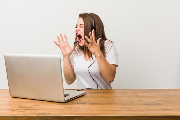 Mulher jovem operador de telemarketing grita alto, mantém os olhos abertos e mãos tensas.