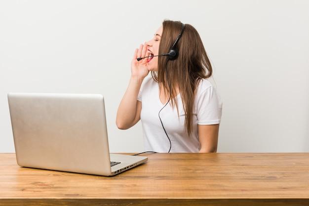 Mulher jovem operador de telemarketing gritando e segurando a palma da mão perto da boca aberta.