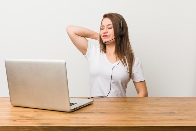 Mulher jovem operador de telemarketing que sofre de dor de garganta devido ao estilo de vida sedentário.