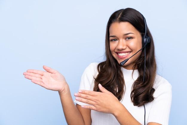Mulher jovem operador de telemarketing sobre parede isolada