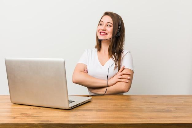Mulher jovem operador de telemarketing sorrindo confiante com braços cruzados.