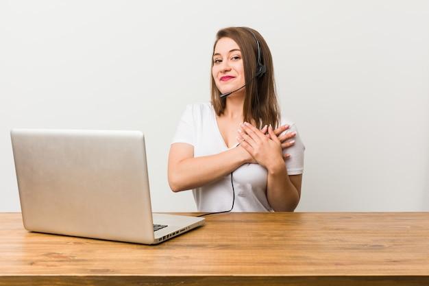 Mulher jovem operador de telemarketing tem expressão amigável, pressionando a palma da mão no peito