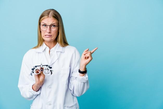Mulher jovem optometrista russa chocada em azul apontando com o dedo indicador para um espaço de cópia.