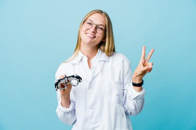 Mulher jovem optometrista russa em azul alegre e despreocupada, mostrando um símbolo de paz com os dedos.