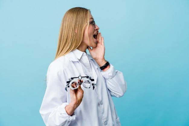 Mulher jovem optometrista russa em azul gritando e segurando a palma da mão perto da boca aberta.