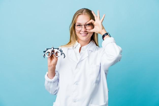 Mulher jovem optometrista russa em azul mostrando sinal de bom sobre os olhos