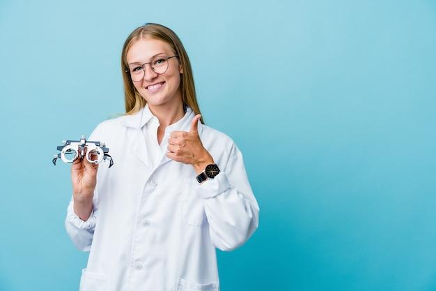 Mulher jovem optometrista russa em azul sorrindo e levantando o polegar
