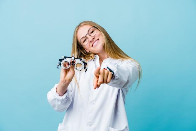 Mulher jovem optometrista russa em sorrisos alegres azuis, apontando para a frente.