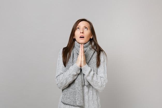 Mulher jovem orando de suéter cinza, lenço cruzou as mãos, olhando para cima isolado no fundo da parede cinza. estilo de vida de moda saudável, emoções sinceras de pessoas, conceito de estação fria. simule o espaço da cópia.