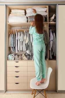 Mulher jovem organiza o armazenamento na prateleira superior de um guarda-roupa. mala e travesseiros no mezanino. armazenamento de roupas.