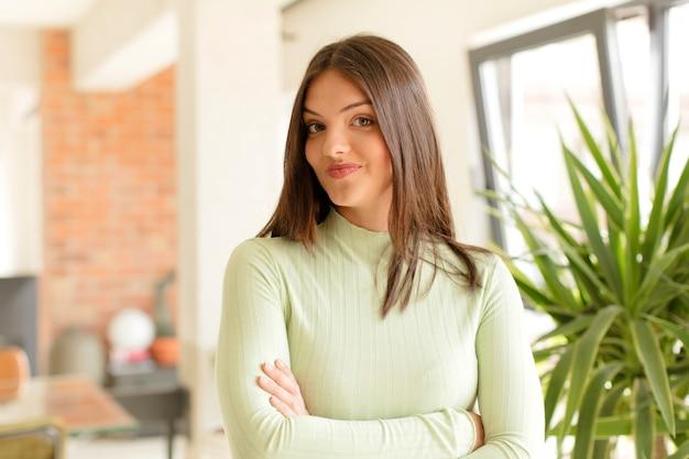 Mulher jovem orgulhosa, confiante, atrevida e arrogante, sorrindo e se sentindo bem-sucedida