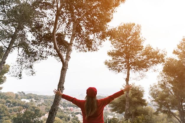 Mulher jovem, outstretching, dela, mãos, olhar, paisagem