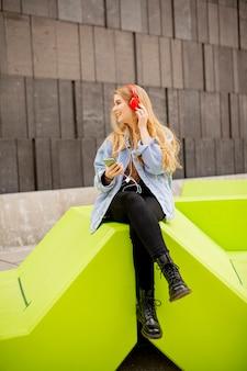 Mulher jovem ouve música de um celular em um banco público moderno em viena, áustria