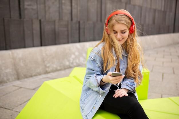 Mulher jovem ouve música de um telefone celular em viena, áustria